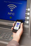 Withdrawing money atm with mobile phone a NFC terminal Royalty Free Stock Photos