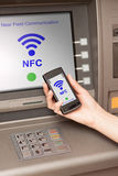 Withdrawing money atm with mobile phone a NFC terminal. Withdrawing money from atm with a mobile phone a NFC terminal Stock Photos