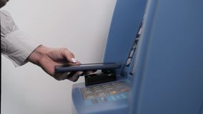 Withdrawing money from atm with a mobile phone a NFC terminal office shopping mall terminal airport close up. Withdrawing money from atm with a mobile phone a stock video