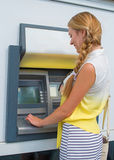 Withdrawing money from an ATM. Stock Photos