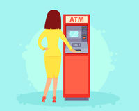 Withdrawing money from an ATM. Young woman withdraws money from an ATM. Vector illustration Stock Image