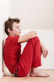 Withdrawn tired boy in red pants and shirt Stock Photography