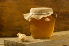 withdrizzler de cristal de la miel del tarro en fondo de madera Fotos de archivo