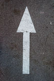 White arrow. White and long arrow on the asphalt Royalty Free Stock Images