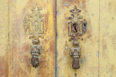 Withered door with iron hands as  knockers Royalty Free Stock Photo