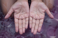 Withered hands of young girl after swimming Stock Photo