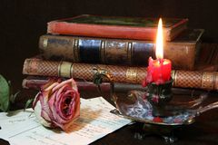 Withered rose with candle flame and antique book