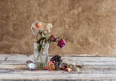 Withered rose in glass and watch on wooden background Royalty Free Stock Photo