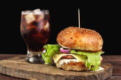 Withglass бургера колы с льдом на деревянной разделочной доске Стоковое Фото
