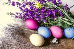 Withr pintado dos ovos da páscoa o ramalhete de flores selvagens roxas na esteira da palha Fotos de Stock