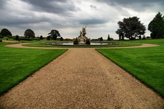 Witley Court garden with fountain. Witley Court fountain with statue. Green grass and trees. Dramatic clouds Stock Photography
