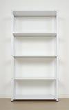 Witmetaalrek dichtbij de muur, lege planken Stock Foto