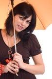 Witn hermoso de la mujer joven un paraguas anaranjado Fotografía de archivo