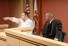 Witness at trial. Man acting as a witness pointing out someone to the judge stock photos