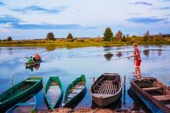 Witrussische Jongen die van Oude Boten bij Zonsondergang van een de Zomerdag vissen Royalty-vrije Stock Fotografie