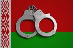 Witrussische vlag en politiehandcuffs Het concept naleving van de wet in het land en bescherming tegen misdaad stock afbeelding
