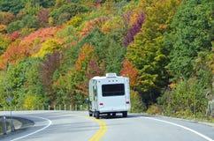 Witte Aanhangwagen op Weg die met Kleurrijke Bomen wordt gevoerd Stock Afbeelding