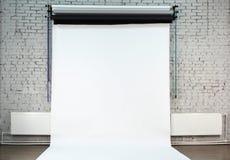 Witte achtergrond op bakstenen muur binnen studio stock afbeelding