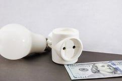 Witte adapter op een grijze achtergrond, een gloeilamp en dollars royalty-vrije stock afbeeldingen