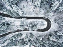 Witte auto die een extreme windende weg in wintertijd doorgeven Stock Foto
