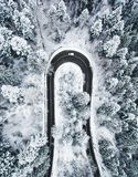 Witte auto die een extreme windende weg in wintertijd doorgeven Stock Fotografie