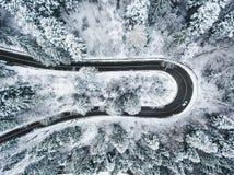 Witte auto die een extreme windende weg in wintertijd doorgeven Royalty-vrije Stock Afbeeldingen