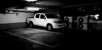 Witte auto op parkeerterrein in de bouw met licht stock foto