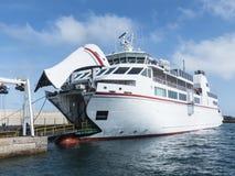 Witte autoveerboot die bij de pijler met open ships'sboog ligt Stock Foto's