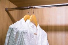 Witte badjassen die in garderobe hangen Stock Fotografie