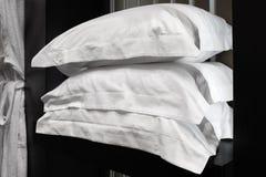 Witte badjassen, hoofdkussens die, handdoeken, in houten kast van de dienstruimte hangen in hotel Stock Afbeelding