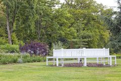Witte bank in gemodelleerde, rijpe Engelse tuin Stock Foto's