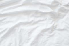 Witte beddegoedbladen of witte de textuurachtergrond van de stoffenrimpel, zachte nadruk Royalty-vrije Stock Fotografie