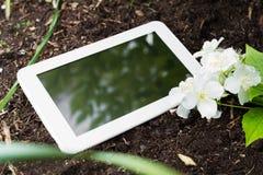 Witte Bedrijfstablet op Grond met Sommige Bloemen Royalty-vrije Stock Foto