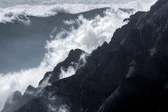 Witte bergwolken boven hoge pieken Stock Foto's