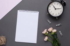 Witte blocnote met bloemen en wekker op grijze achtergrond in uitstekende stijl hoogste mening stock afbeelding