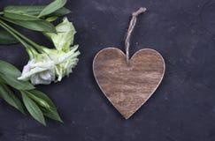 Witte bloemen en bruin houten hart op donkere concrete achtergrond De kaart van de groet Rood nam toe Stock Foto
