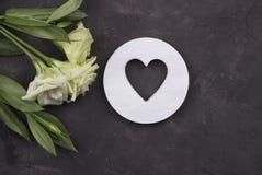 Witte bloemen en houten hart op donkere concrete achtergrond De kaart van de groet Rood nam toe Royalty-vrije Stock Afbeeldingen