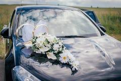 Witte bloemen en trouwringen op de kap van de zwarte auto stock foto's