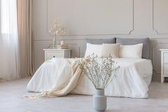 Witte bloemen in vaas in elegant grijs slaapkamerbinnenland met eenvoudig beddegoed royalty-vrije stock foto