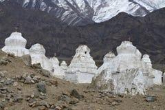 Witte Boeddhistische stupas bevinden zich met een groep die, dicht tegen elkaar tegen een achtergrond van donkere bergen, de bove Royalty-vrije Stock Afbeeldingen