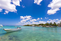 Witte boot dichtbij de rotsachtige kust in Bayahibe, La Altagracia, Dominicaanse Republiek Exemplaarruimte voor tekst Stock Afbeelding