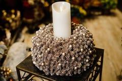 Witte brandende die Kerstmiskaars in een kandelaar van sparappel en ballen wordt gemaakt royalty-vrije stock afbeeldingen