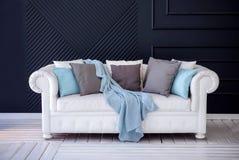 Witte bus met grijze en blauwe hoofdkussens en wollen deken die zich op een witte houten vloer tegen donkerblauwe muur bevinden stock foto
