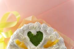 Witte cake op een gekleurde die achtergrond met linten hierboven worden geschoten van stock foto's