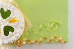 Witte cake op een gekleurde die achtergrond met linten hierboven worden geschoten van royalty-vrije stock afbeelding