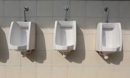 Witte ceramisch van urinoirs in de badkamers van mensen Stock Foto's