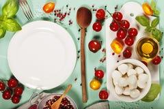 Witte ceramische dienende raad en saladeingrediënten over lichte blu Royalty-vrije Stock Fotografie