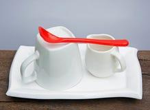 Witte Ceramische Koffiereeks en Rode Plastic Lepel Royalty-vrije Stock Afbeeldingen