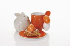 Witte ceramische konijntjeskruik met koffiekop, gebakje en paaseieren Stock Foto's