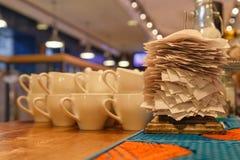 Witte ceramische mokken voor thee en controles van voltooide orden in t royalty-vrije stock afbeelding